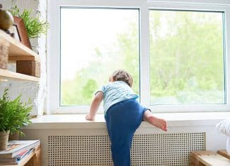 Rear View Of Boy Climbing Up Onto Window Sill
