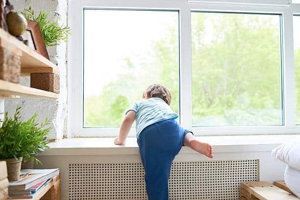 Rear View Of Boy Climbing Up Onto Window Sill