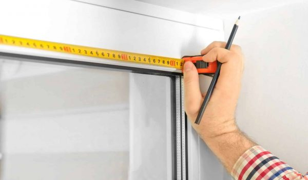 Man Marking Off Window Frame At Home